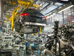 Car body and engine transmission marriage in car factory Stock Photos