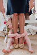 Girl hugging mothers ankles - stock photo