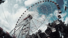Ferris wheel in the amusement park against the backdrop of running thick clouds  - stock footage