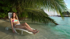 Young slim woman enjoying vacation on a sun lounger on a tropical beach. Stock Footage