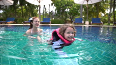 Little girl in the swimming vest floating in the pool with his mother. Stock Footage