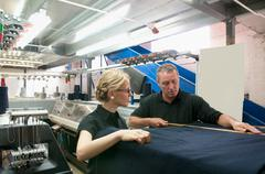 Workers talking in garment factory Stock Photos