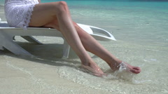 Young woman enjoying vacation on a sun lounger on a tropical beach. Slow motion. - stock footage