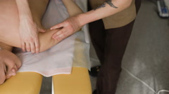 Physiotherapist doing neck massage to his patient in medical office Stock Footage