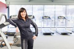 Woman leaning on treadmill at gym Stock Photos