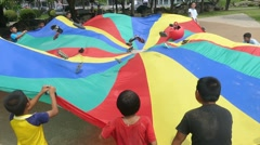 Short Term Missions Team Using Parachute With Asian Children Stock Footage