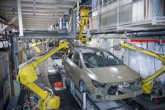 Robots applying sealant to cars in car factory Kuvituskuvat
