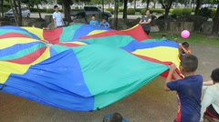 Youth Missions Team Playing Parachute With Asian Children Stock Footage