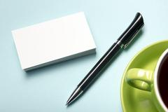 Stock Photo of Business card blank over coffee cup and pen at office table. Corporate