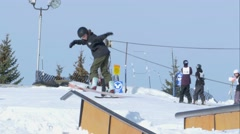 Snowboarder performs railslide during contest. Stock Footage