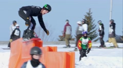 Snowboarder goes over steps obstacle during contest. - stock footage