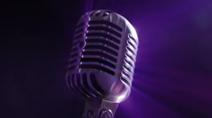 Vintage microphone rotating as it reflects colorful stage light - stock footage