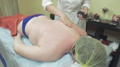 Masseuse make remedial massage of back by one hand to thick woman in saloon - stock footage