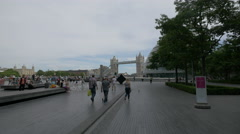 People relaxing and walking on London's riverside near the Tower Bridge Stock Footage