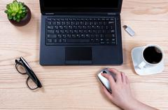 Office desktop setup with female hand holding wireless computer mouse - stock photo