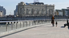 Woman with a dog walking on the promenade in the city Stock Footage