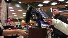 Woman paying credit card for wine in BC Liquor Store Stock Footage
