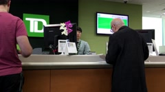 People at service counter talking to the teller inside TD Bank Stock Footage