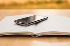 Mobile phone and diary on wood table - stock photo