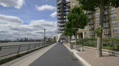 Girl riding bike on a pedestrian alley along River Thames Stock Footage