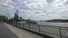 Boats passing on river Thames seen from a pedestrian alley in London Stock Footage