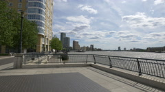 View of Canary Wharf from a pedestrian alley along River Thames, London Stock Footage