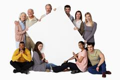 Group of people holding blank notice board - stock photo