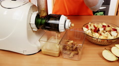 Female hands adding apple fruits in juicer machine 4K Stock Footage