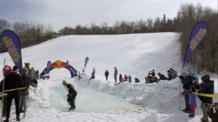 Snowboarder skims across pool of water during the slush cup challenge Stock Footage