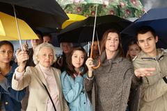Group of people with umbrellas - stock photo