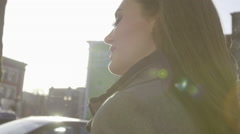 A beautiful young woman walks down a city street Stock Footage