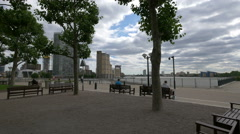 Relaxing on benches on the riverside in Canary Wharf, London Stock Footage