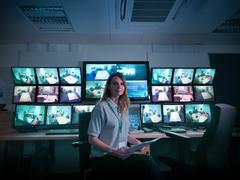 Stock Photo of Portrait of student with screens in forensics training facility