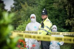 Policeman and forensic scientists at crime scene with police tape in foreground Stock Photos