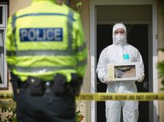 Forensic scientist holding evidence box containing firearm at crime scene, Stock Photos