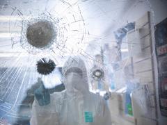 Forensic scientist dusting for fingerprints in broken glass  at crime scene Stock Photos