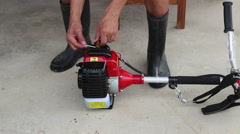 The gardener check the spark plug of lawn trimmer machine Stock Footage
