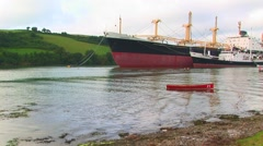 Container ship with small red boat - stock footage