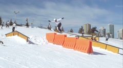 Snowboarders go over obstacles during rail jam contest. - stock footage
