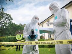 Forensic scientists in discussion at crime scene, one holding camera, policeman Stock Photos