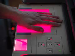Close up up man scanning hand for fingerprints on machine in laboratory - stock photo