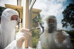 Forensic scientists dusting window for finger prints at crime scene Stock Photos