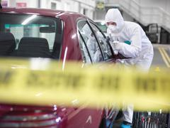 Forensic scientist dusting car for finger prints at crime scene Kuvituskuvat
