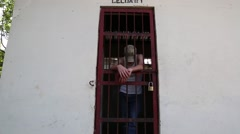 Prisoner leaning on door of a Latin American jail cell Stock Footage