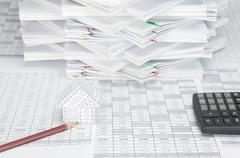 House and pencil have calculator and overload paperwork as background Stock Photos