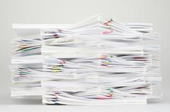 Overload document with colorful paperclip on white table Stock Photos