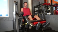 Man Does Leg Extensions At The Gym Stock Footage