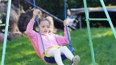 Young girl plays on her swing in her garden, in slow motion - stock footage