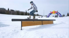 Snowboarder performs 180 railslide during contest. Stock Footage