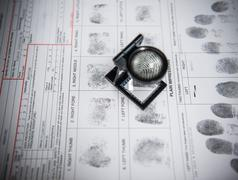 Fingerprints with loupe on arrest form in forensic laboratory - stock photo